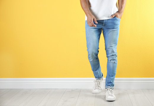 Young man in stylish jeans near color wall with space for text, focus on legs