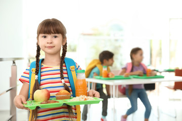 Girl holding tray with healthy food at school canteen