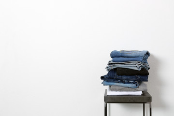 Stack of different jeans on table against white background. Space for text