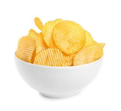 Bowl of tasty ridged potato chips on white background