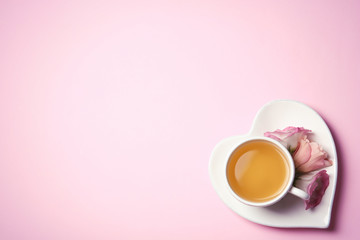 Cup of tea and flowers on color background, top view with space for text