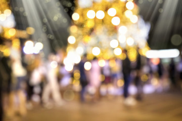 Blurry background image of defocused outdoor Christmas decorations with colorful lights and crowd of people in busy city street at night