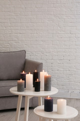 Burning candles on tables in living room