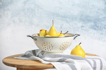 Colander with pears on table against color background