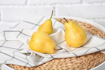 Ripe pears on table near brick wall