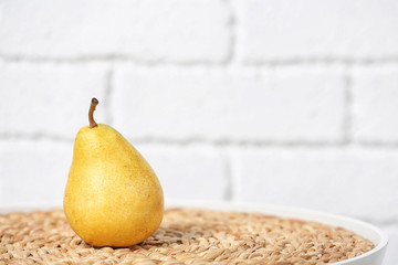 Ripe pear on table near brick wall. Space for text