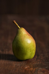 Tasty ripe green pear on wooden background