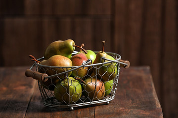 Basket with ripe pears on wooden table
