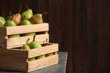 Wooden crates with ripe pears on table. Space for text