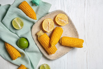 Flat lay composition with corn cobs and citrus fruits on white wooden background