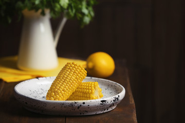 Plate with ripe corn cobs on table against dark background. Space for text