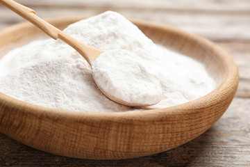Plate with baking soda on wooden table, closeup