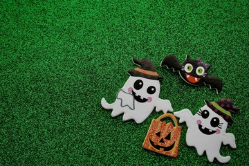 two ghosts holding a pumpkin treat bag with a bat flying above on a green background