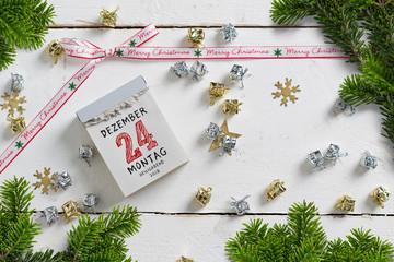 weihnachtliche Dekoration und Abreißkalender mit dem 24.12.2018 auf weißem Holzuntergrund