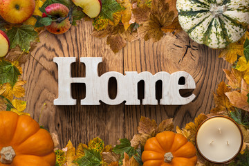 "word ""home"" on wooden background with autumn decoration"