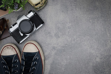 Top view travel concept with retro camera films,other items on grey cement background with copy space