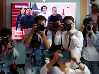 Photographers take pictures of people watching the televised broadcast in Seoul