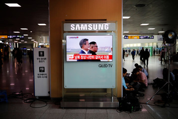 A television screen shows a broadcast in Seoul