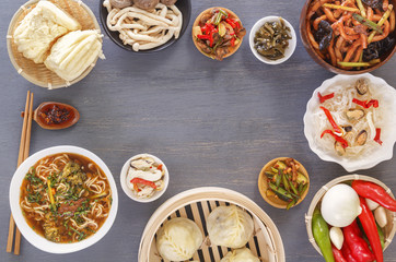 Dishes of Chinese cuisine in assortment. Steam dumplings, noodles, salads, vegetables, mushrooms, seafood. Top view. Copy space