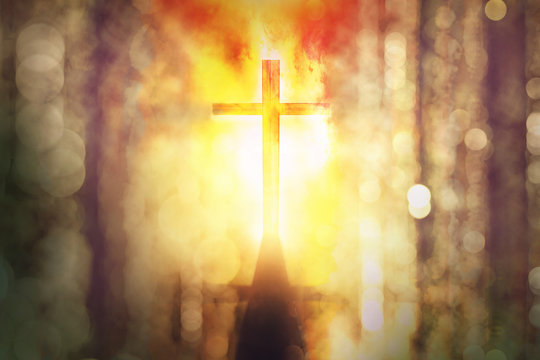 silhouette of burning cross with rays of sunlight background