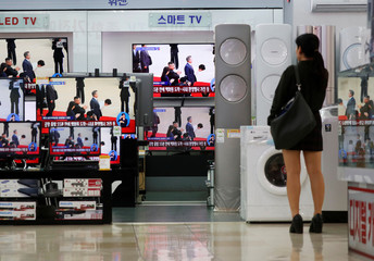 A woman looks at television screens showing a broadcast at an electronics store in Seoul