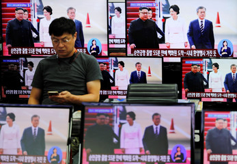 A man is seen among television screens showing a broadcast at an electronics store in Seoul