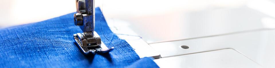 Panorama, Nähfuß einer Nähmaschine mit Leinenstoff blau, Textfreiraum