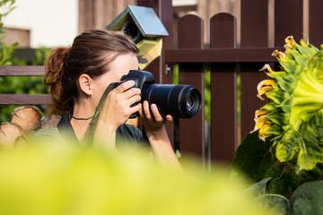 Frau beim fotografieren von einer Sonnenblume im Garten, Hobby und Beruf Fotograf