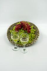 frische Grüne und rote Weintrauben in einem Korb mit Weißweingläsern.