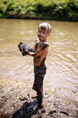 Muddy Little Boy Child Laughing as He Swims and Plays Outside in River