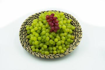 frische Grüne und rote Weintrauben in einem Korb.