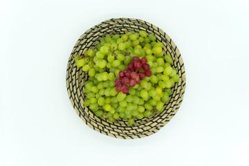 Grüne und rote Weintrauben in einem Korb.