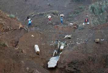 Residents carry supplies as they hike after a road was eroded by a landslide caused by Typhoon Mangkhut at a small-scale mining camp in Itogon