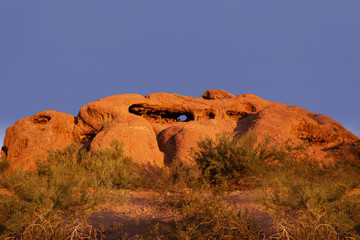Wall Mural - Papago Park known as the hole in the rock glowing red orange as sunsets over Phoenix,Arizona,USA