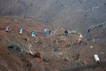 Residents hike after a road was eroded by a landslide caused by Typhoon Mangkhut at a small-scale mining camp in Itogon