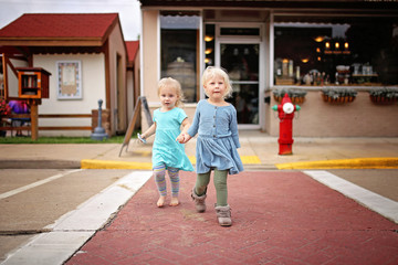Two little Toddler Girls Holding Hands Crossing the Road on a small Town Main Street