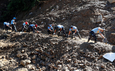 Policemen continue their search for missing miners in a landslide caused by Typhoon Mangkhut at a small-scale mining camp in Itogon
