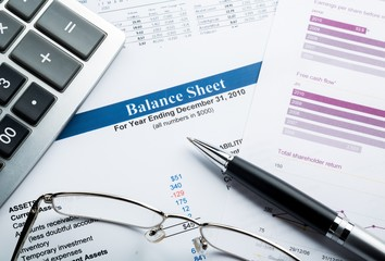 Calculator, Glasses And Pen On Balance Sheet Close-up