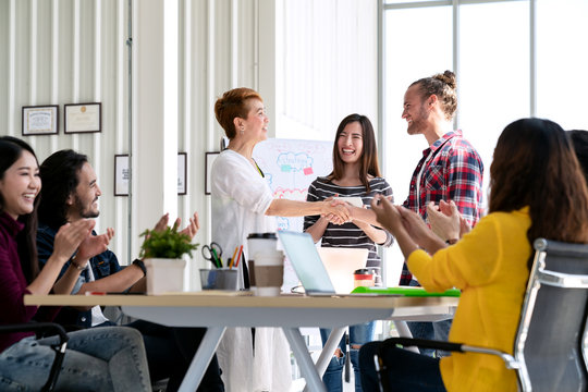 Attractive mature asian woman shaking hand with young beard hipster caucasian with welcome new employee, congratulating successful or happy with business deal while team applauding support together.