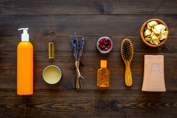 Cosmetics for hair care with jojoba, argan or coconut oil. Bottles and pieces of oil on dark wooden background top view pattern