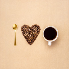 I love coffee / Creative concept photo of heart made of coffee with cup and spoon on brown background.