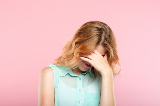 facepalm embarrassment and shame emotion. ashamed smiling girl covering her face with a hand. young beautiful woman portrait on pink background.