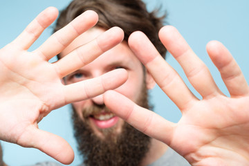 man shutting out from view. private life and paparazzi concept. guy putting hands forward blocking unwanted attention. portrait of bearded hipster on blue background.