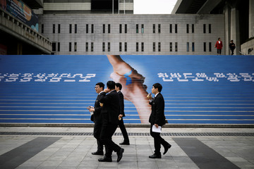 Men walk past a public installation wishing for the success of the inter-Korean summit in central Seoul