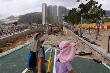 Children walk through a damaged path after Super Typhoon Mangkhut hit Hong Kong
