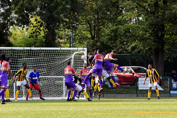 Clapton CFC players (blue jersey) attack the defence of Ealing Town during away game in East Acton, in London