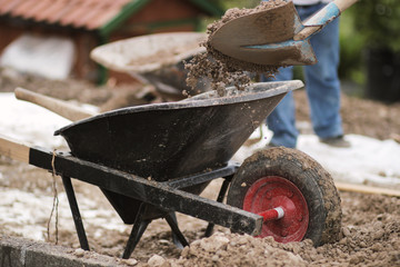 gravel filled in with shovel into wheelbarrow