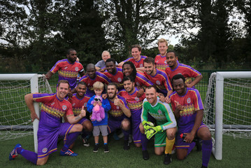 Clapton CFC players pose for a picture with one of their youngest supporter after winning 2-1 away game against Ealing Town in East Acton, in London