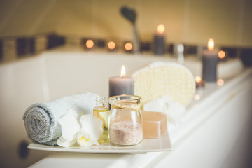Obraz White ceramic tray with home spa supplies in home bathroom for relaxing rituals. Candlelight, salt soap bar, bath salt in jar, massage, bath oil in bottle, blue rolled towel, natural sponge.  - fototapety do salonu