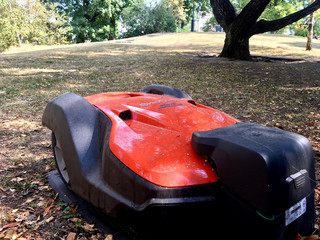 A Husqvarna robotic lawn mower is placed in its docking station in the Humlegarden park in Stockholm